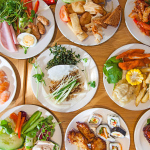 A selection of Chinese buffet foods served on a spread of white plates